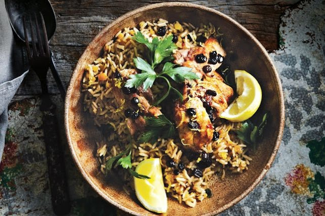 Rice and chicken in a bowl topped with parsley and lemon zest