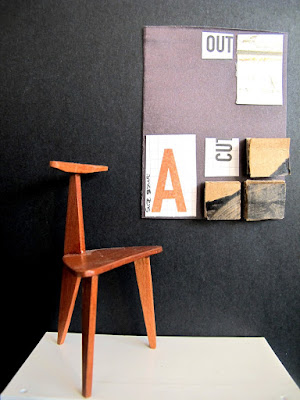 Modern miniature gallery space with a one-of-a-kind wooden chair displayed on a plinth in front of a black and brown collage.