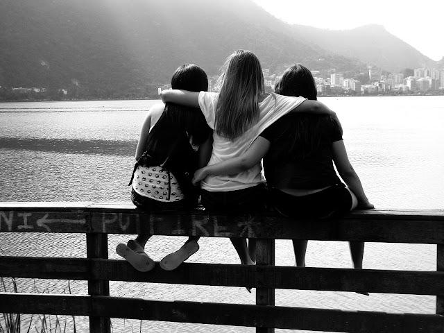 Amigos sentados num alambrado olhando um rio abraçados