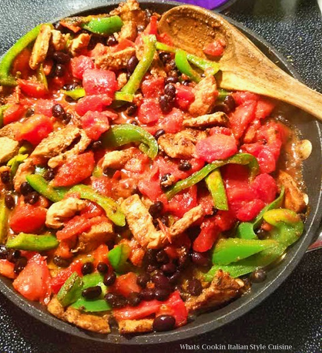 this is a pan of black beans, peppers, chicken and tomatoes for a Mexican filling dinner with flour tortilla