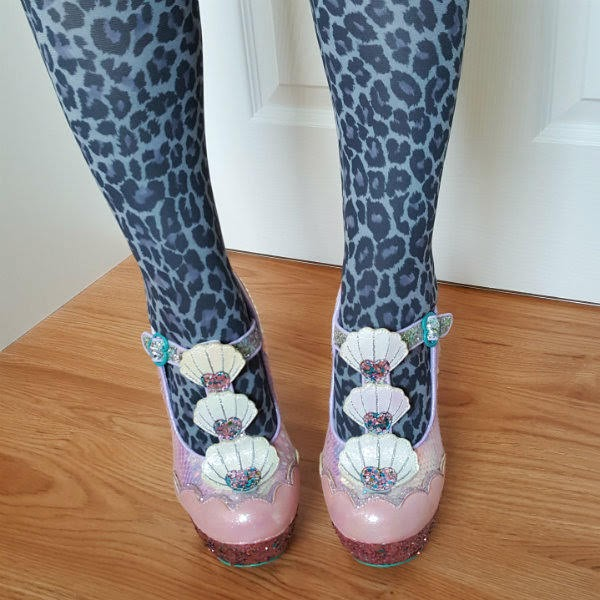 pink shoes with shell applique and glitter platform being worn with leopard print tights