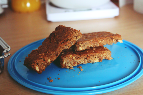 peanut butter granola bars lying on a blue plastic tupperware lid in a pile