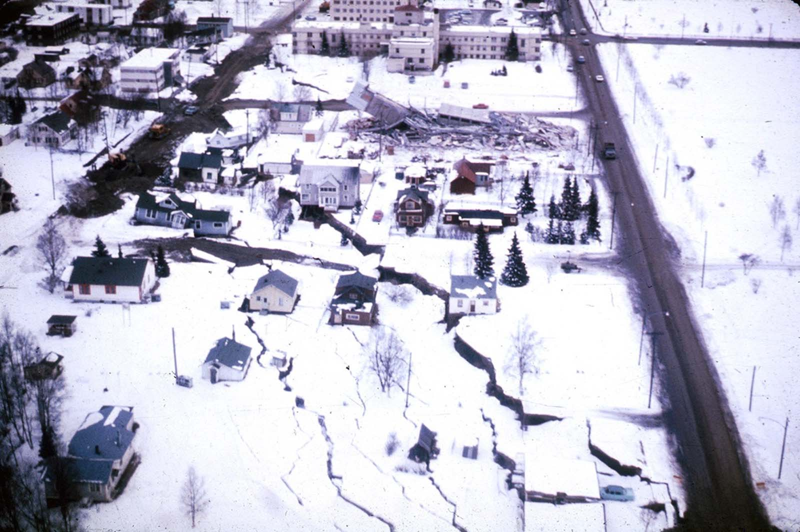 The head of the L Street landslide in Anchorage. The land on the left side sank 7 to 10 feet in response to 11 feet of horizontal movement of the lower section of the slide. A number of houses were undercut or tilted by subsidence of the graben. Note also the collapsed Four Seasons Apartment Building and the undamaged three-story reinforced concrete frame building behind it, which are on more stable ground.