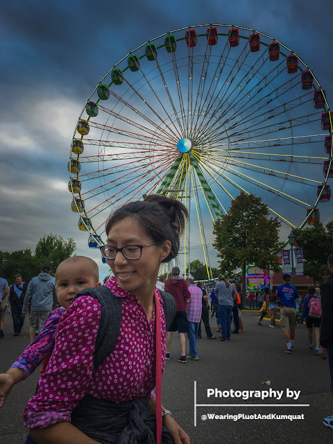 Image of a smiling tan skin bespectacled Asian woman wearing a toddler on her back in a meh dai with black chambray straps. Behind them is a large multi-colored ferris wheel. It is an overcast day.