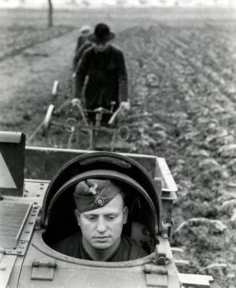 "Second World War. German soldier in a tank. [possibly a Renault UE, a French made ""Armored Tractor"" or ""Infantry Supply Vehicle""; designed for utility work, used and modified by the Germans]. German soldiers are helping the French farmers plough their fields. France, 1941. From the collection of the Nationaal Archief of the Netherlands."