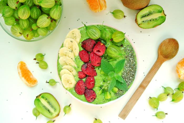 smoothie w misce zielone, udekorowane bananem, malinami, agrestem i nasionami chia