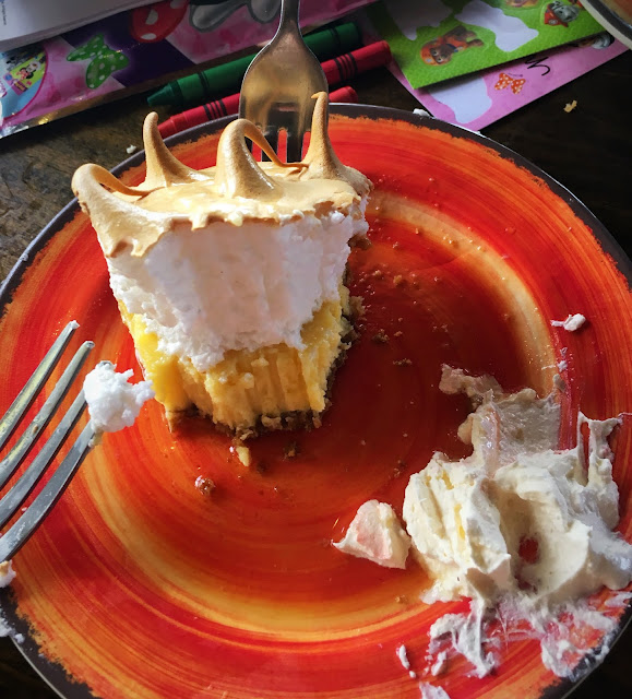 A more than half eaten slice of Key Lime Pie with a dollop of whipped cream that's also more than half eaten on an orange plate. Two forks, and crayons, stickers, and activity pack in the background.