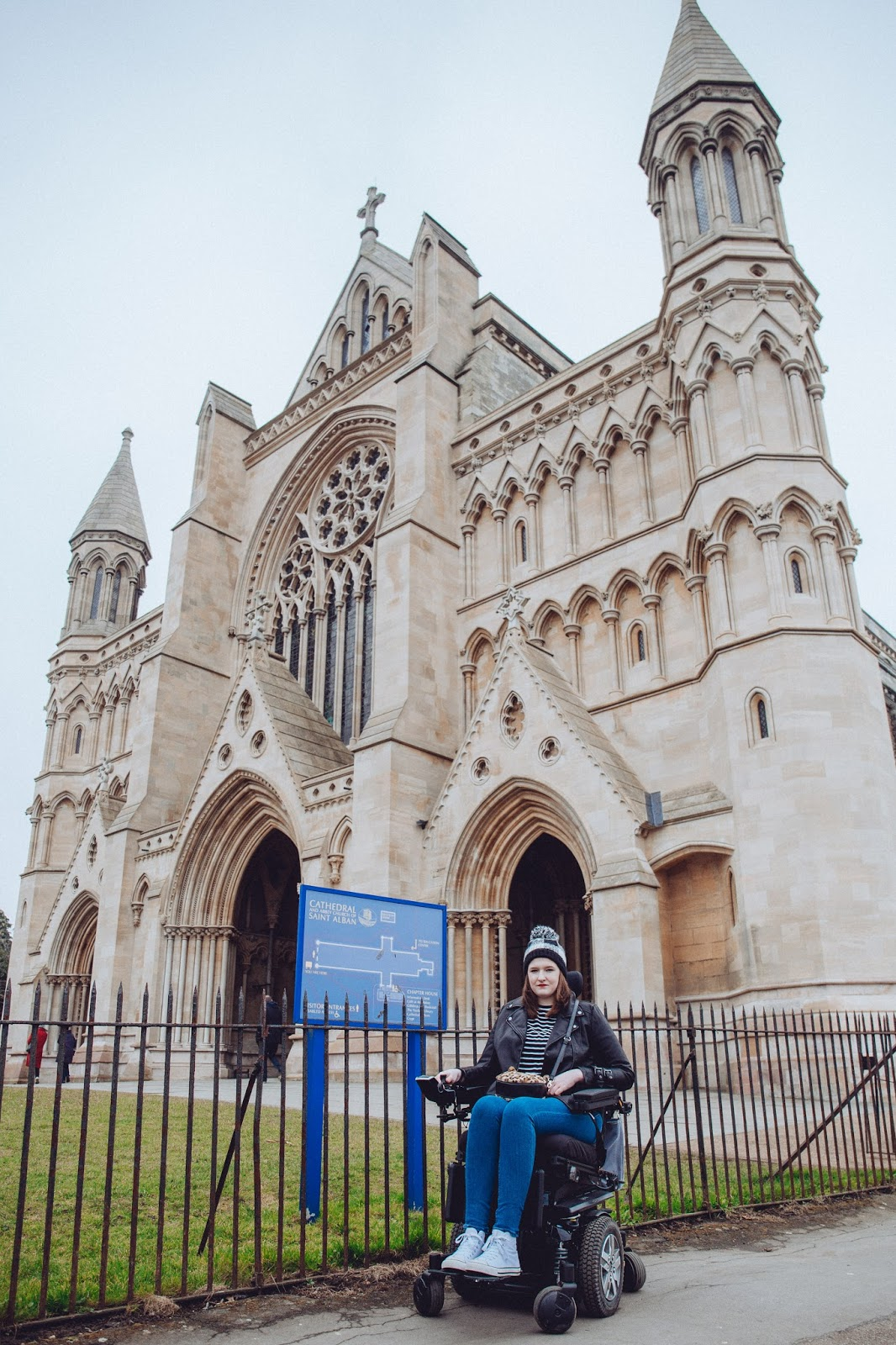 Image of Shona, sitting in her powerchair, in front of a cathedral with metal fencing directly behind her.