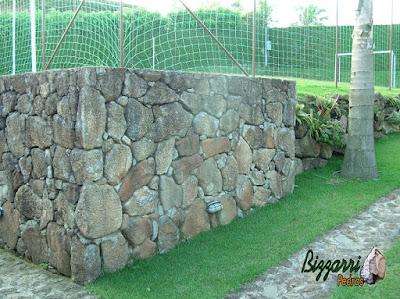 Muro de pedra com pedra bruta para formar o platô para a construção do campo de futebol com a execução do paisagismo em sítio em Mairiporã-SP.