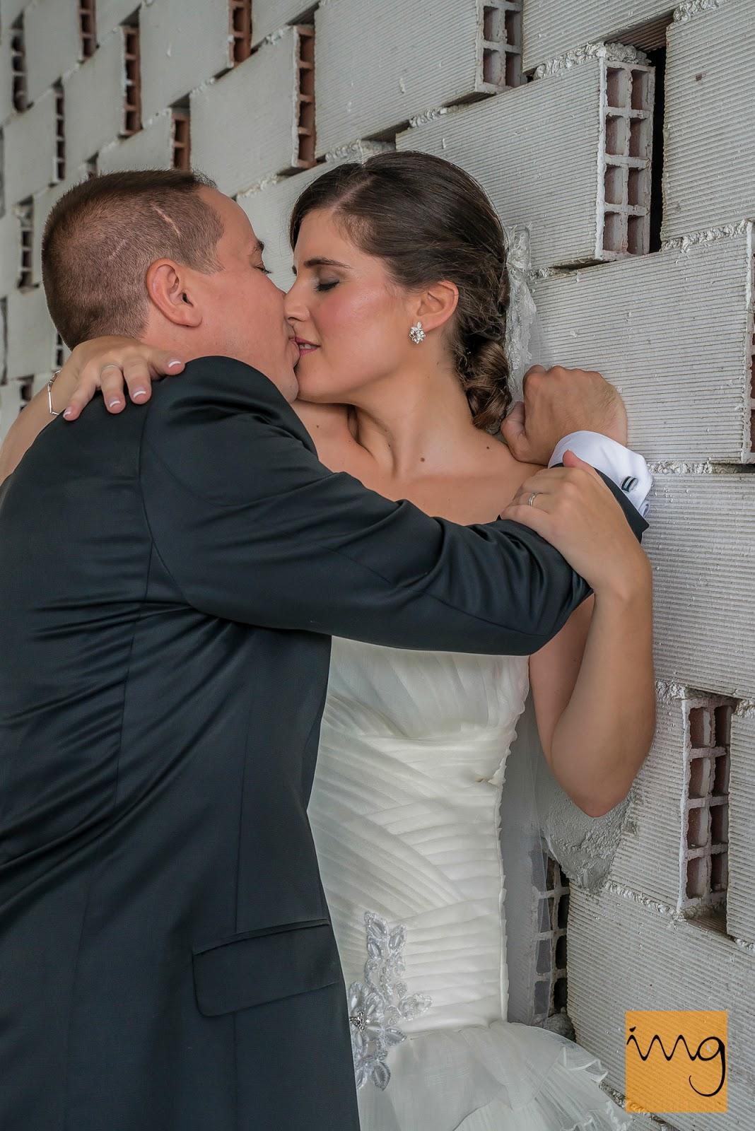 Fotografía de un beso apasionado en una pared de ladrillo