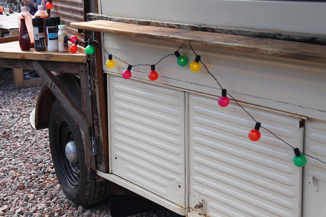 multi coloured bulb string lights on trailor at street food festival