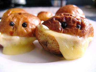 Two roasted potatoes, cut in half with melted cheese in the middle and peppercorns inserted to look like eyes.