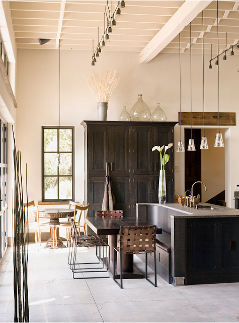 Industrial kitchen with white beamed ceiling and rustic armoire with glass bottles