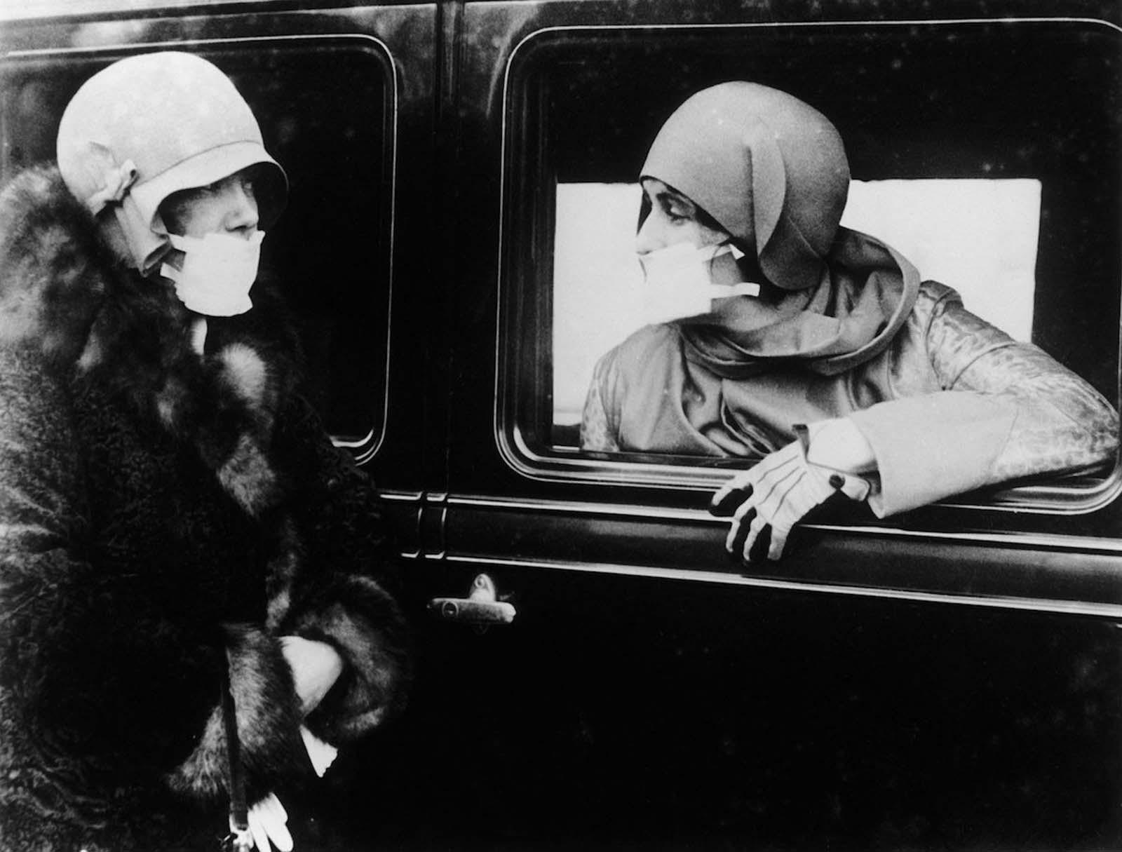 Two women speak through flu masks during the epidemic. 1918.