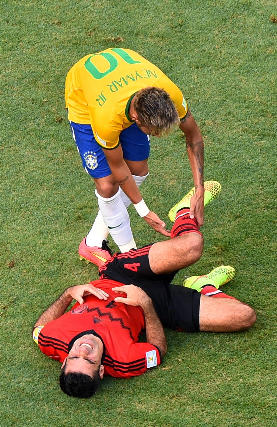 Brazil's Neymar, left, attends Mexico's Rafael Marquez after a foul during the group A World Cup soccer match between Brazil and Mexico at the Arena Castelao in Fortaleza, Brazil, Tuesday, June 17, 2014.