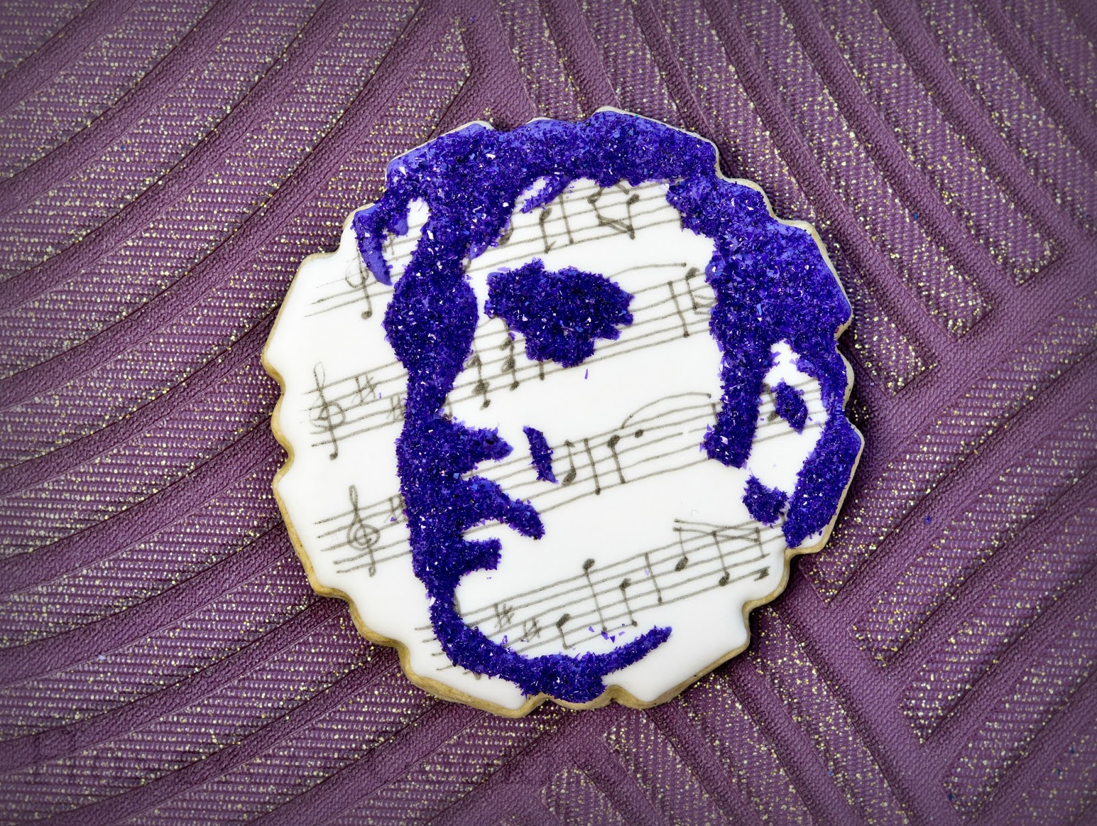 Elvis silhouette cookie in glitter on hand drawn musical notation background, by Honeycat Cookies.
