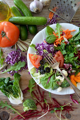 A colorful salad with a fork in a white bowl and vegetables surrounding it. Photo by Nadine Primeau.