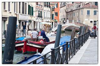 Velencei hajók egy csatornán híddal a háttérben