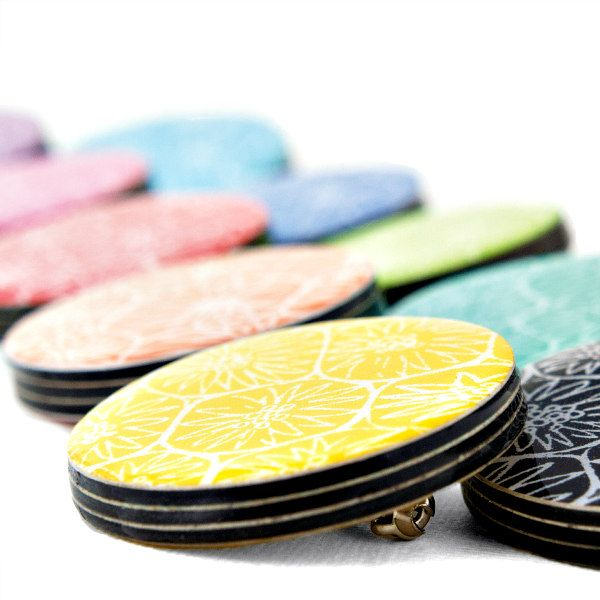 Colorful brooches made of card layers and resin with a printed design