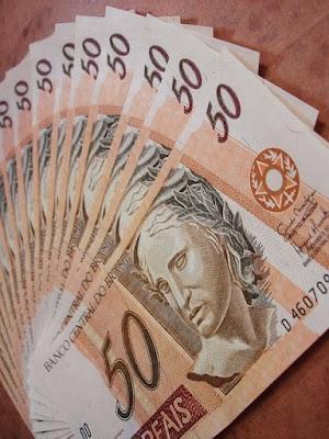 Notas sobrepostas de cinquenta reais.