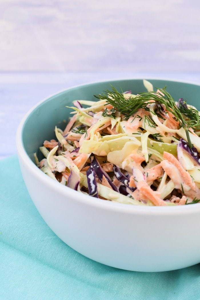 Close up of Vegan Coleslaw with Fresh Herbs in pale blue bowl on pale blue napkin