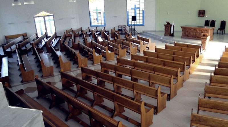 Igreja totalmente vazia, mostra somente os bancos e o pulpito