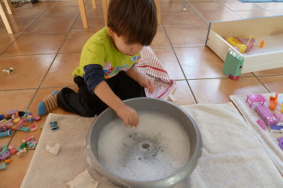 Child washing toys in a bowl