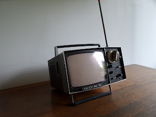 A vintage Sony portable television sits on a wooden surface.