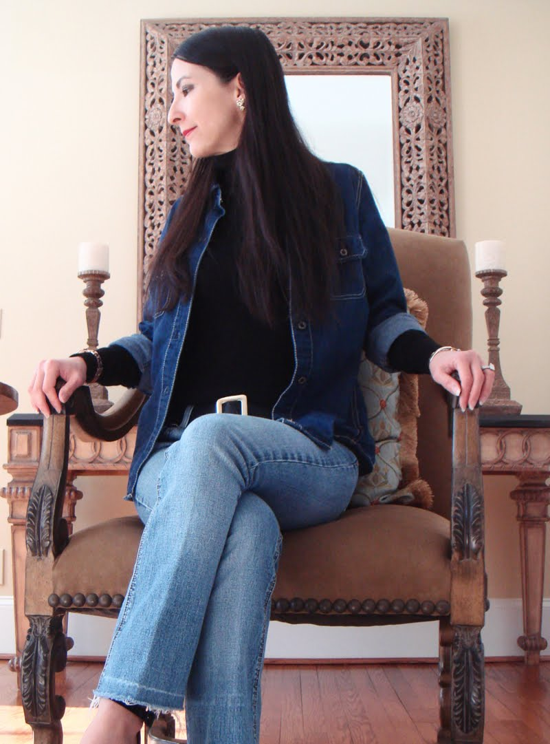Denim On Denim Outfit. Seated in a large beige chair.