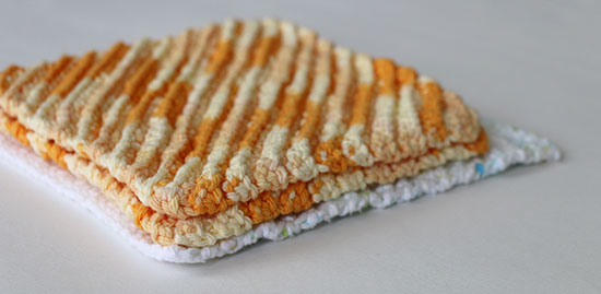 Two crocheted cotton orange washcloths or dishcloths stacked on top of a white cloth on a white background.