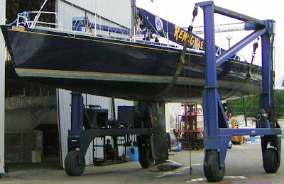 70 racing sailboat with torpedo keel in slings of straddle crane