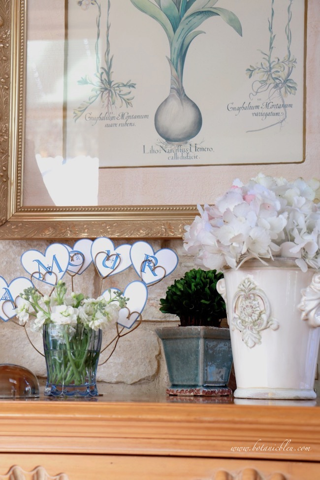 Valentine's vignette uses flowers, hearts, love banner