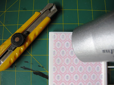 Hairdryer pointed at the wallpaper on the wall of a Lundby Smaland dolls' house.