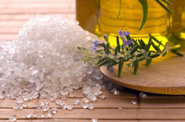 recuadro de madera sobre el cual se muestra un puñado de sal marina y un ramillete de hierba
