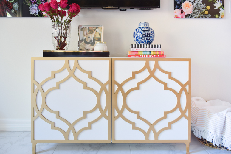 An IKEA Besta TV stand with Khloe O'verlays in a master bedroom suite with black, white and gold decor touches.