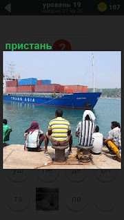 На пристане стоит судно с контейнерами и рабочие сидят на берегу
