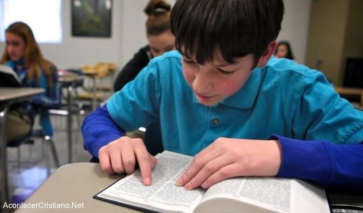 Alumno estudiando Biblia en escuela
