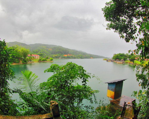 Tinuku.com Travel Lake Poso white golden sandy beach and green blue water surrounded by hills and orchids forest