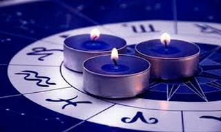 Imagen de tres velas encima del logotipo de los signos del zodiaco