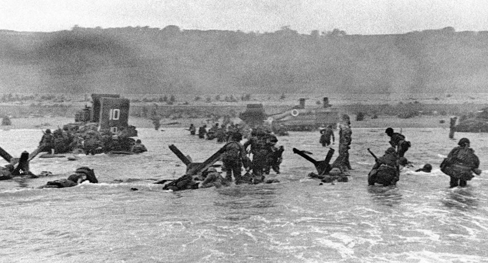 Some of the first assault troops to hit the beachhead in Normandy, France take cover behind enemy obstacles to fire on German forces as others follow the first tanks plunging through the water towards the German-held shore on June 6, 1944.