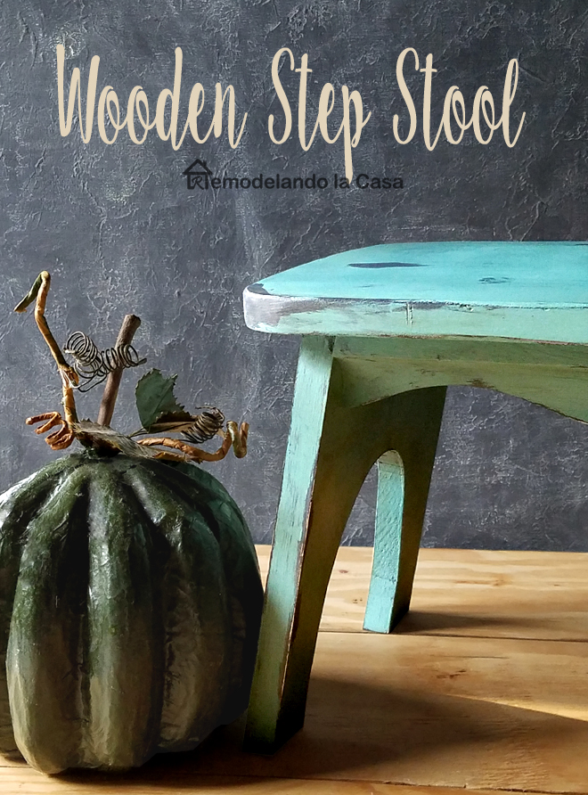 Pumpkin on floor, chalkboard background, wooden floor, blue step stool, green pumpkin