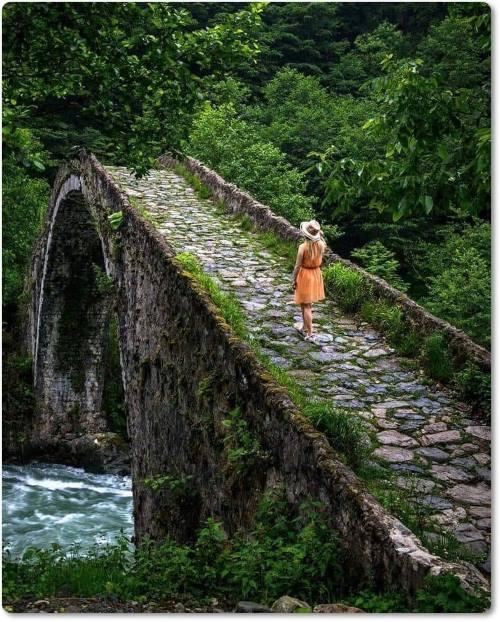 Ponte de pedra, por entre as árvores, sobre ela uma jovem caminhando solitária.