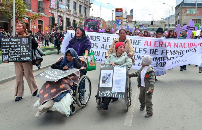 UNO DE LOS NIÑOS, HIJO DE UNA SOBREVIVIENTE DE FEMINICIDIO, AYUDA A SU MADRE A AVANZAR EN LA SILLA DE RUEDAS EN UNA MARCHA CONTRA LA VIOLENCIA CONTRA LAS MUJERES.