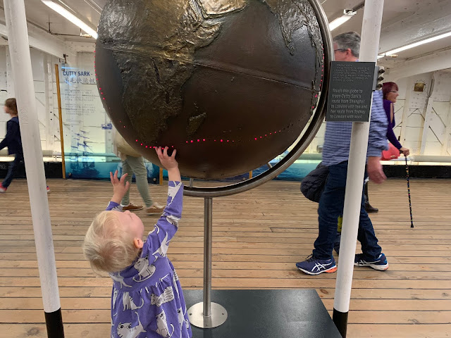 A toddler reaching up to touch a globe with red lights to indicate the route of the Cutty Sark