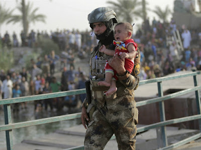 An Iraqi soldier carries a displaced kid from Ramadi on the outskirts of Baghdad, Iraq.