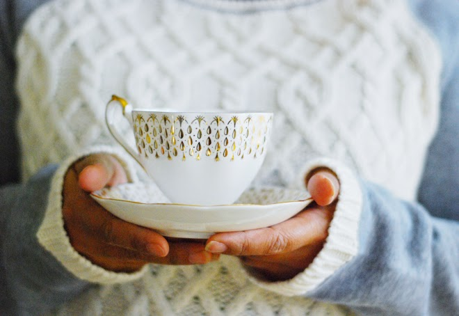 Vintage gold white tea cup in hand