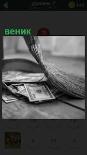 веником подметают деньги на полу, доллары