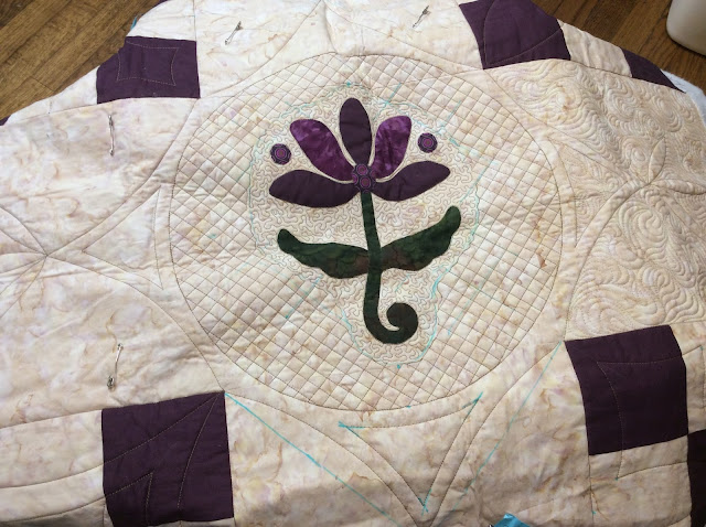 applique quilt with crosshatching done with rulers on a sewing or domestic machine.