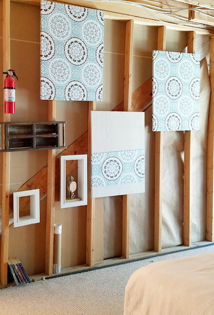 wooden boxes and fabric panels on 2 x 4 wall in basement
