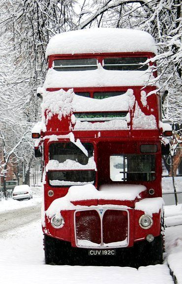 Snow covered red double-decker bu